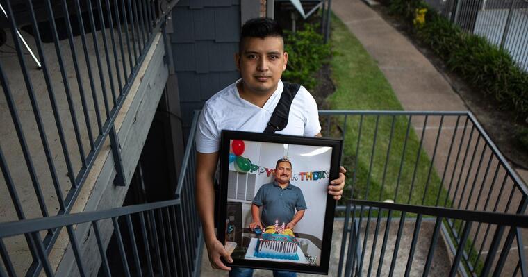 Cristóbal Onofre muestra una foto enmarcada de su padre, quien murió abruptamente por COVID-19 este mes, frente a su casa en Houston.