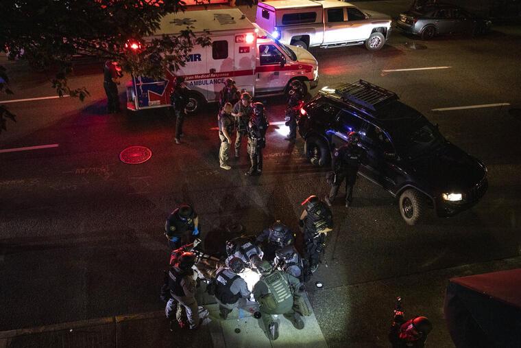 Médicos socorren a un hombre que perdió la vida tras ser tiroteado el sábado por la noche en Portland, Oregon, mientras se registraban enfrentamientos entre grupos rivales.