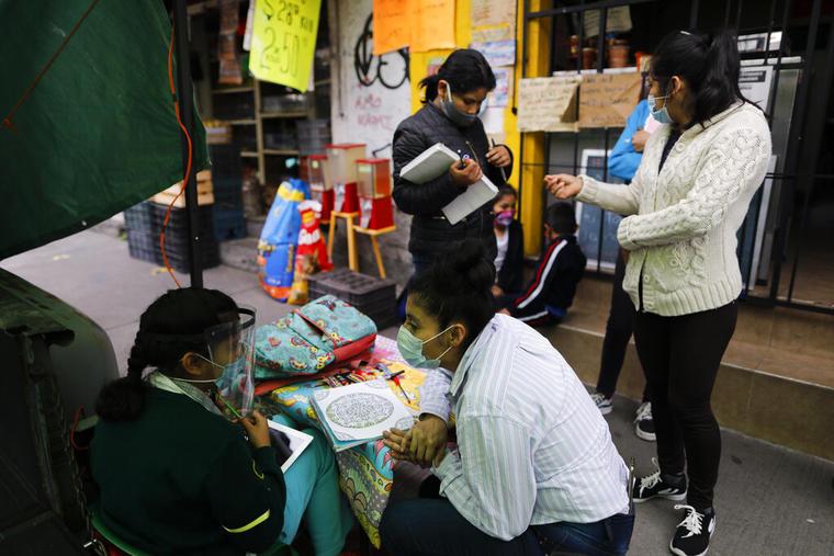"""Dalia Dávila Neri, que maneja """"Tortillerías La Abuela"""", asesora el pasado viernes a la estudiante Aidé Joselín Hernández Moreno mientras ella aprende con una tableta donada afuera de la tienda."""