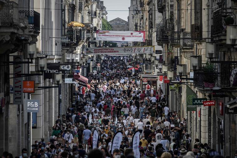Peatones, algunos con mascarillas protectoras, caminan por una calle llena de tiendas en Burdeos, Francia.