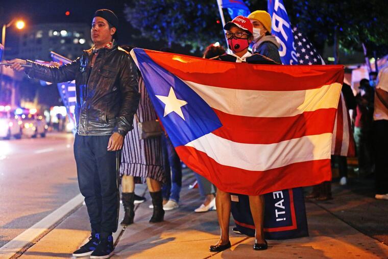 Mirna García llevaba una bandera de Puerto Rico, mientras esperaba los resultados de las elecciones junto a otros partidarios del presidente Donald Trump frente al restaurante Versailles, en Miami, durante la noche de las elecciones.