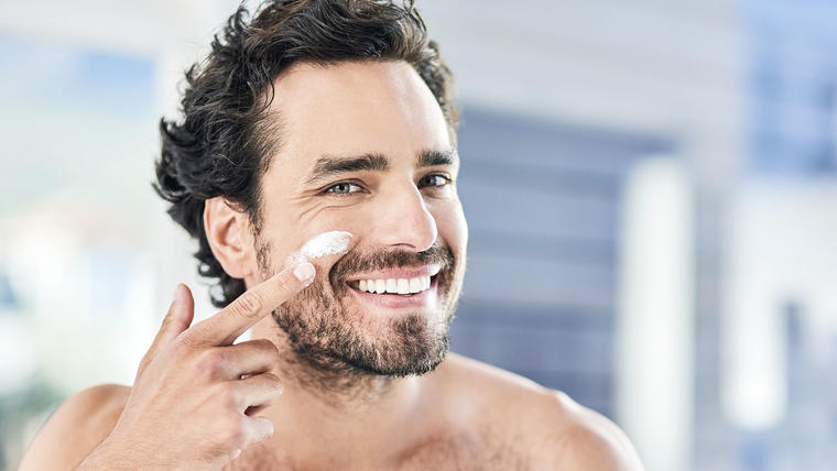 Hombre aplicando crema facial