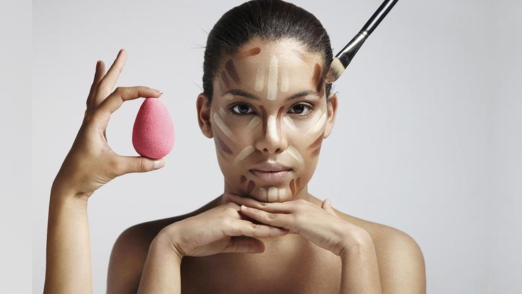 Mujer con esponja y brocha de maquillaje