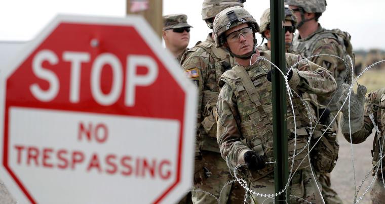 Miembros del ejército de EEUU colocan alambre de púas en un campamento temporal para las tropas  en el puente internacional en Donna, Texas el 4 de noviembre de 2018.