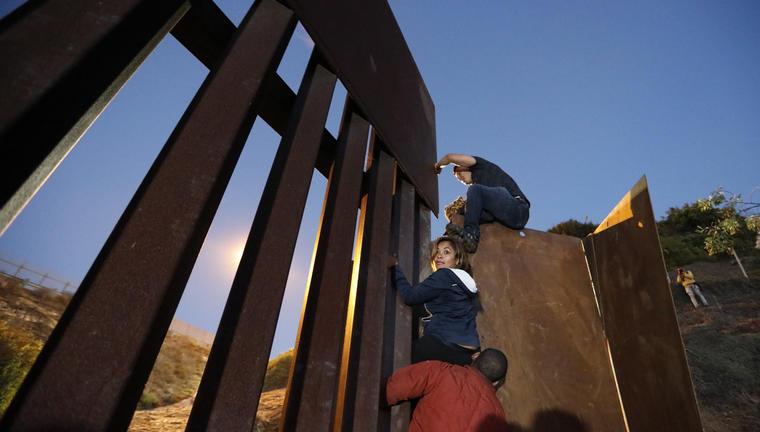 Personas escalando el muro fronterizo/AP