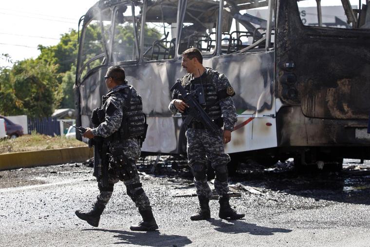 Policías estatales pasan junto a un autobús carbonizado luego de que los bomberos extinguieran las llamas en Guadalajara, México