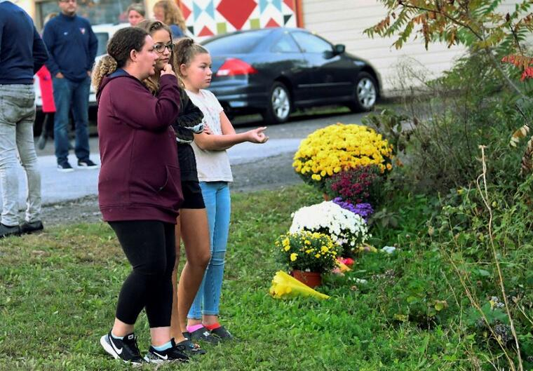 Amigos de las víctimas que murieron en un fatal de limusina colocan flores en la intersección en Schoharie, Nueva York.