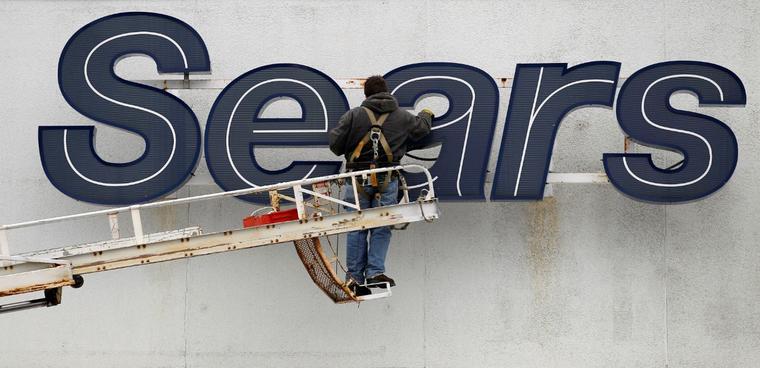 Un trabajador repara un cartel de Sears en una imagen de archivo.