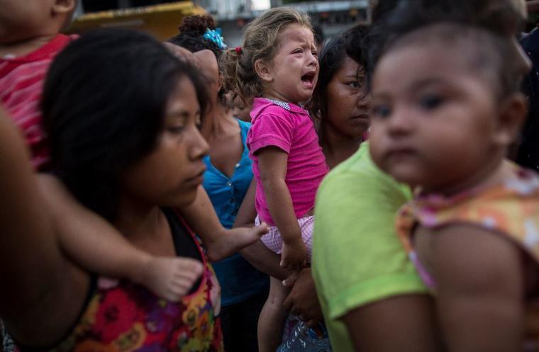 Una niña, de dos años, espera este domingo con su madre a recibir comida donada en Tapanatepec, México.