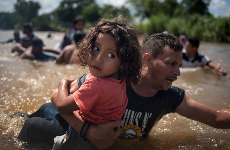 Una segunda caravana migrante en ruta a los Estados Unidos cruza a pie el río Suchiate que separa Guatemala y México.