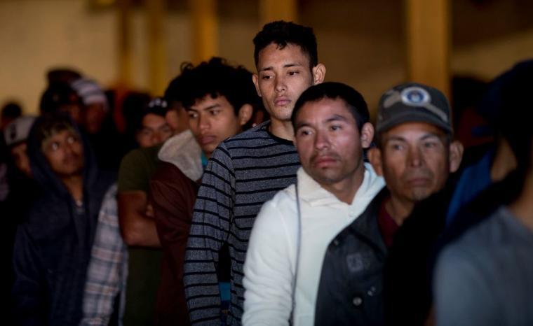 Migrantes hondureños hacen cola para desayunar en un almacén en el centro de Tijuana, México, este martes 18 de diciembre.