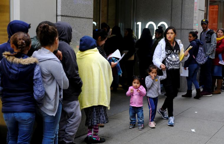 Cientos de personas desbordan este jueves una acera mientras esperan en línea frente a una oficina de inmigración de EE. UU. en San Francisco.