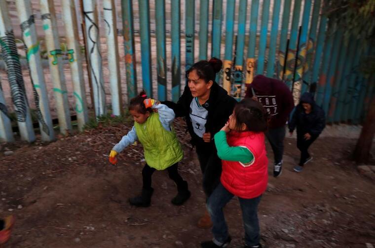 Una mujer hondureña con sus hijos el pasado diciembre en Tijuana cerca del muro fronterizo de EE. UU.