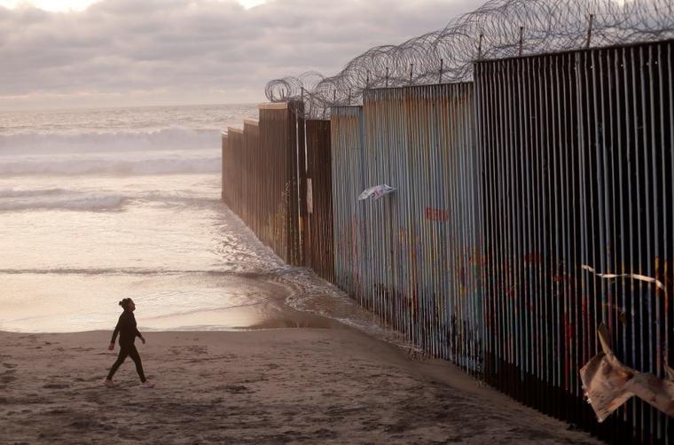 En esta foto de archivo del 9 de enero de 2019, una mujer camina en la playa junto al muro fronterizo cubierto con alambre de afeitar en Tijuana, México.