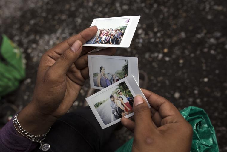 Un miembro de un grupo de migrantes LGTB mira fotos que documentan su viaje en el camino a Sayula, México, el 3 de noviembre de 2018.