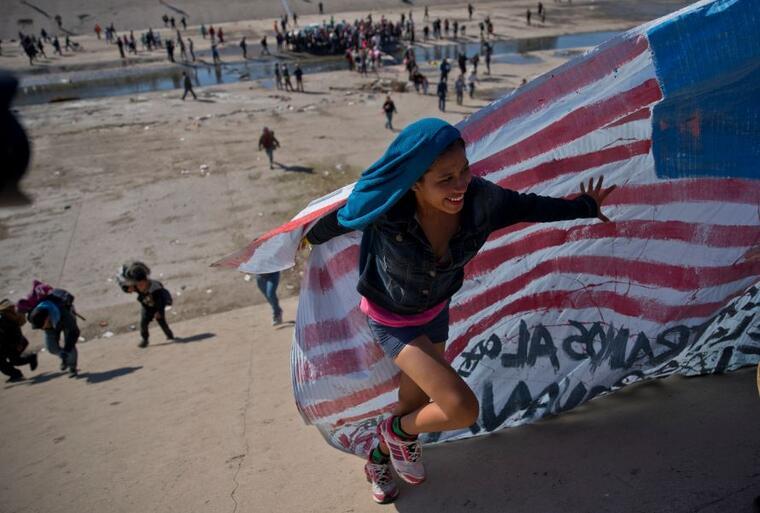 Foto de archivo del 25 de noviembre de 2018, una migrante con una bandera estadounidense en la frontera de México con Estados Unidos cerca del cruce fronterizo de Chaparral en Tijuana.