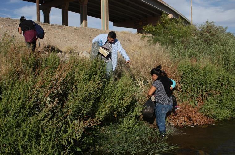 Migrantes centroamericanos cruzan este lunes el Río Bravo por la línea de Paso del Norte, en Ciudad Juárez (México).