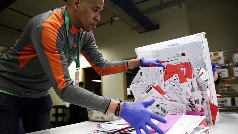 El trabajador electoral Erick Moss clasifica las boletas de votación por correo para las primarias presidenciales en las elecciones del condado de King en Renton, Washington, el 10 de marzo de 2020.