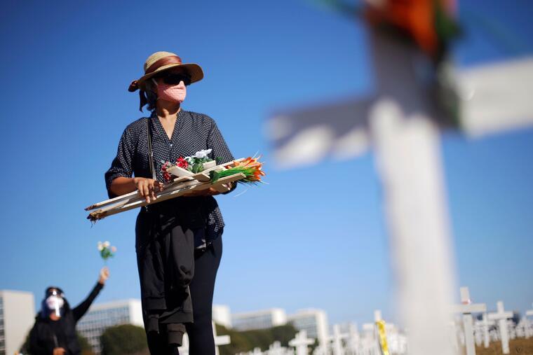 Una mujer sostiene cruces que simboliza a los muertos por coronavirus frente al Congreso en Brasilia.