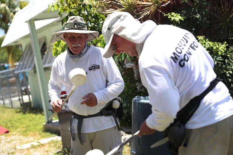 Meredith Kruse and Billy Ryan, del departamento del control de mosquitos en los cayos de Florida, inspeccionan un vecindario en Key Largo, Florida, donde se han confirmado 11 cases de dengue.