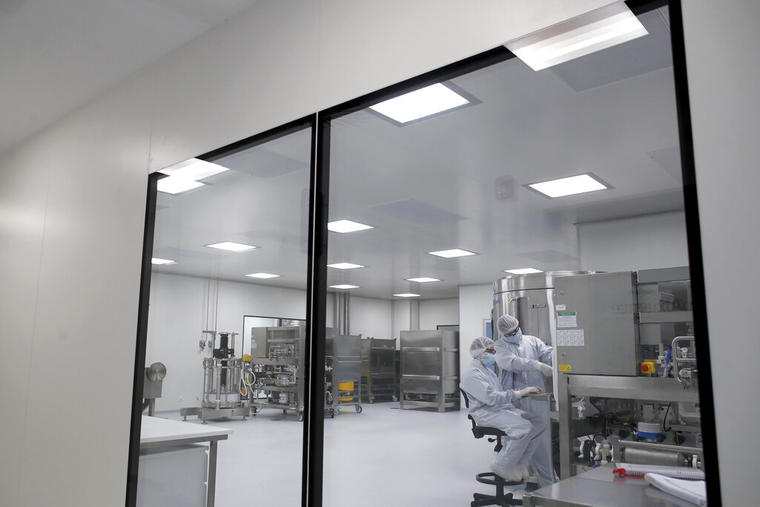 Técnicos de laboratorio trabajan en una vacuna experimental contra el COVID-19