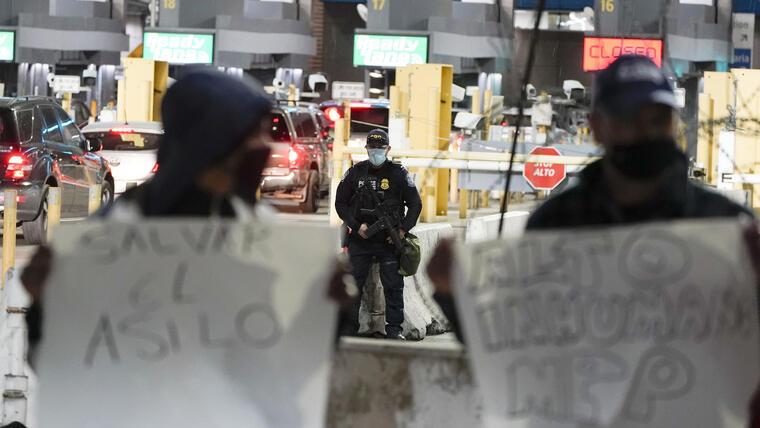 Agentes fronterizos protegen el paso durante una vigilia migrante realizada el 19 de enero de 2021.