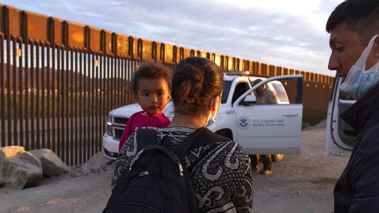 Una familia migrante de Brasil espera ser procesada por agentes de la Patrulla Fronteriza de EE.UU. después de atravesar una brecha en el muro fronterizo de México en Yuma, Arizona, el 10 de junio de 2021.