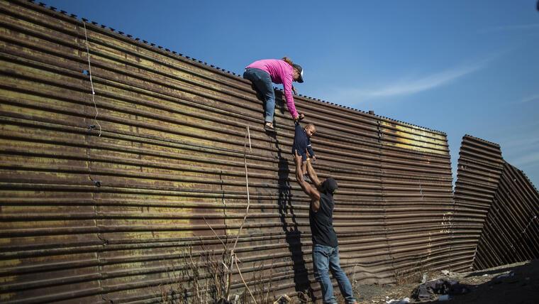 Dos adultos y un bebé intentan cruzar el muro fronterizo entre México y Estados Unidos.