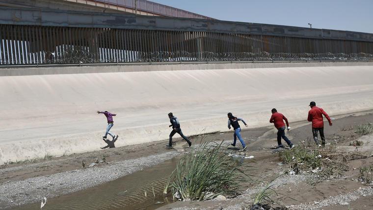 Migrantes cruzan el Río Bravo para entregarse a las autoridades estadounidenses y solicitar asilo, en la frontera entre Estados Unidos y México entre Ciudad Juárez y El Paso.
