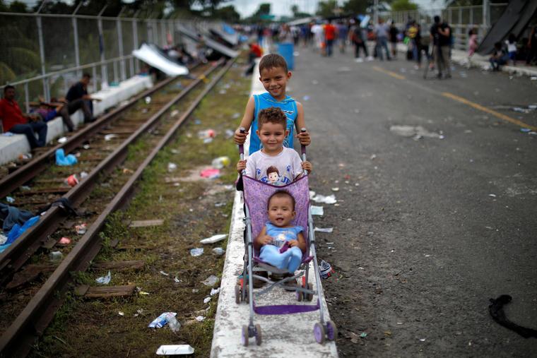 Tres niños hondureños esperan en la ciudad guatemalteca Tecún Umán para pedir asilo en México. Los menores migrantes viajaban junto a sus padres.