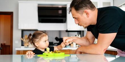 Papá dándole de comer a su hija