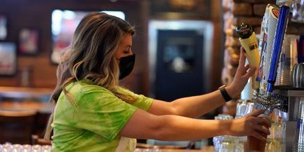 Una bartender sirve una cerveza para sus clientes en un bar de Indianapolis, el 14 de marzo de 2021.