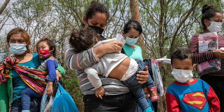 Varias mujeres que buscan solicitar asilo esperan el transporte de los agentes de la Patrulla Fronteriza después de cruzar el Río Bravo hacia Texas el 25 de marzo de 2021 en Hidalgo, Texas.
