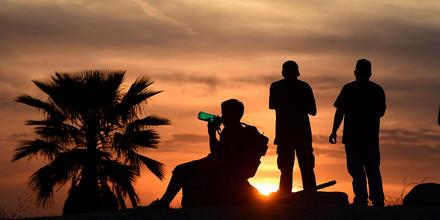 La gente ve la puesta de sol cuando un niño bebe de una botella de agua el 15 de junio de 2021 en Los Ángeles, California, mientras las temperaturas se disparan en una ola de calor al comienzo de la temporada.