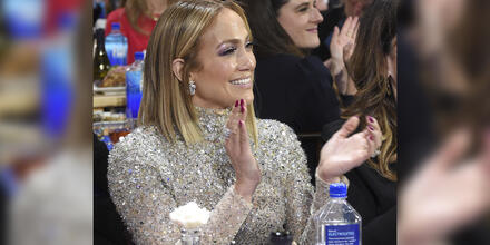 Jennifer Lopez celebrando y aplaudiendo en ceremonia de festival de cine.