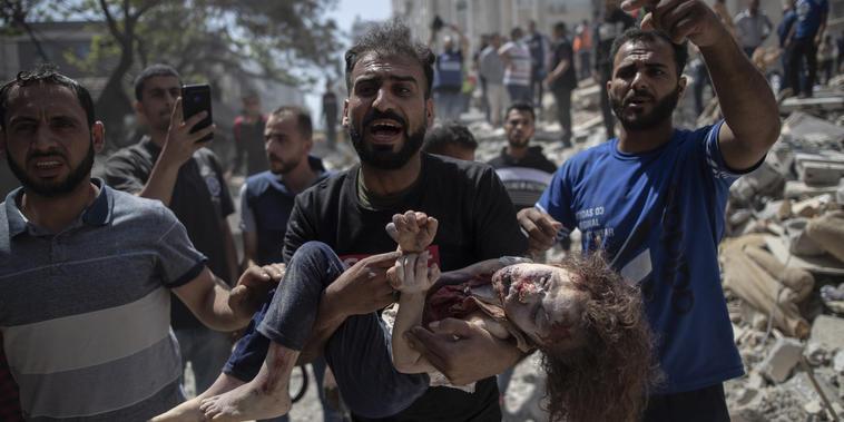Un hombre palestino carga a un niño muerto en Gaza.