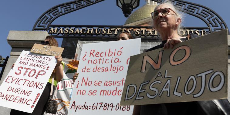 Personas de una coalición por la justicia en las viviendas llevan carteles de protesta contra los desalojos durante una conferencia de prensa junto a la legislatura de Massachusetts, en Boston, el 30 de julio del 2021.