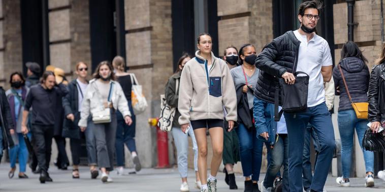 Un grupo de personas en Nueva York con y sin mascarilla