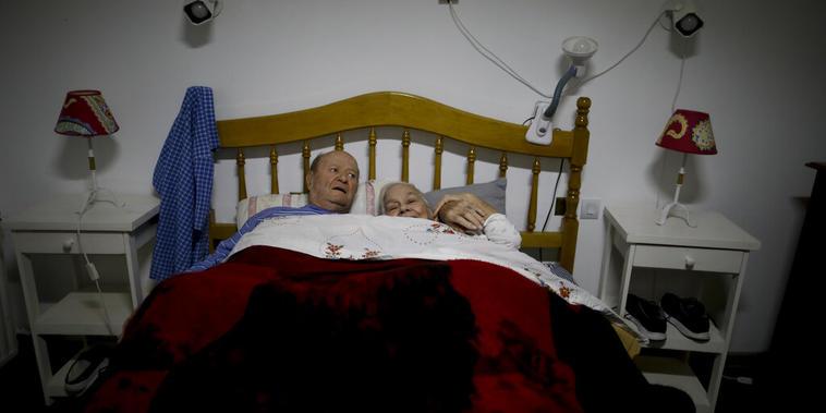 Fermín Urban y Catalina Pisicelli en la cama de su habitación de la residencia Reminiscencias, donde se conocieron el año pasado en Tandil, Argentina, el 4 de abril de 2021.