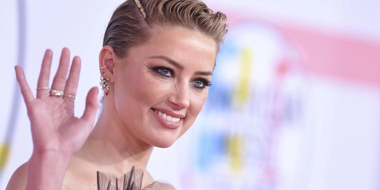 Amber Heard sonriendo, mostrando joyas.
