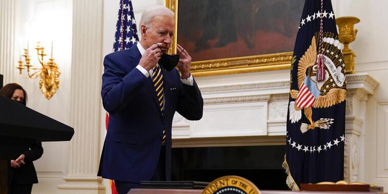 El presidente, Joe Biden, se coloca su mascarilla antes de firmar una serie de órdenes ejecutivas.