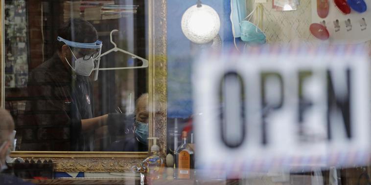 Un barbero usa una mascarilla y un escudo protector le corta el cabello a un cliente en una barbería en Northbrook, Illinois, el viernes 29 de mayo de 2020, en medio de restricciones y medidas de protección por la pandemia.