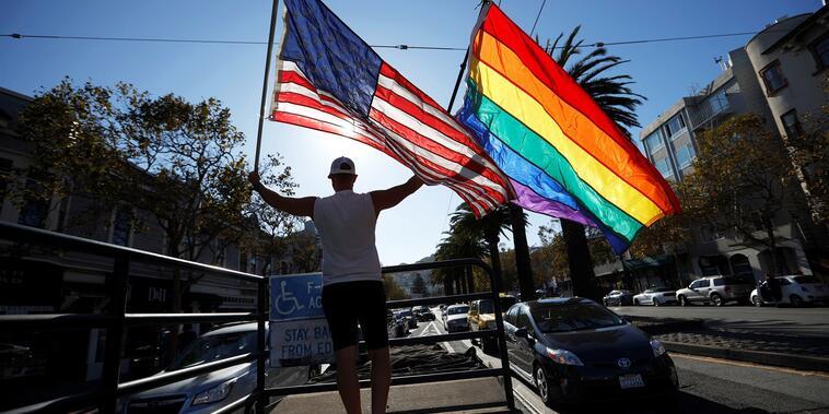 Un residente de San Francisco ondea la bandera de Estados Unidos y la LGBTQ en esa ciudad de California, en apoyo a Joe Biden, el 7 de noviembre de 2020.