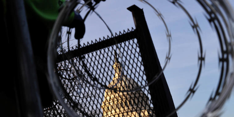 Los trabajadores instalan alambre de púas encima de la valla que rodea el Capitolio a raíz de los disturbios del 6 de enero. La seguridad en torno al edificio se mantendrá debido a las renovadas amenazas.