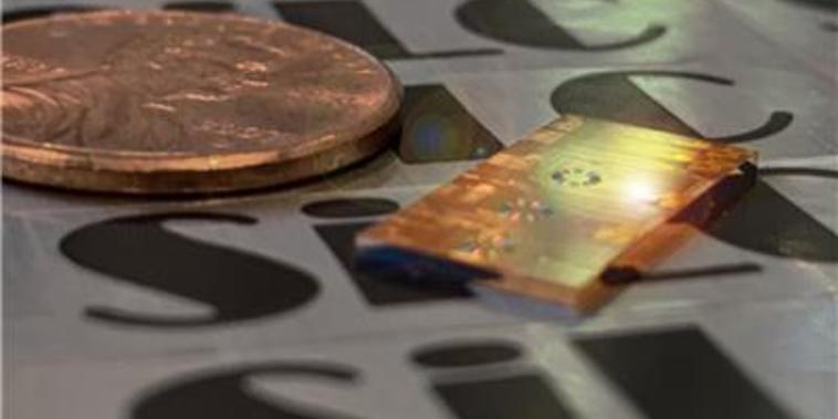 Imagen de un microchip al lado de una moneda de un centavo