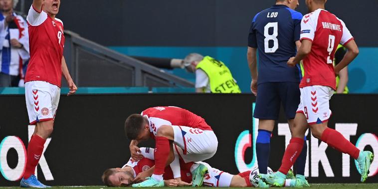 Jugadores de la selección de Dinamarca tratan de socorrer a su compañero Christian Eriksen, quien se desvaneció durante un partido ante Finlandia, el 12 de junio de 2021 en Copenhague.