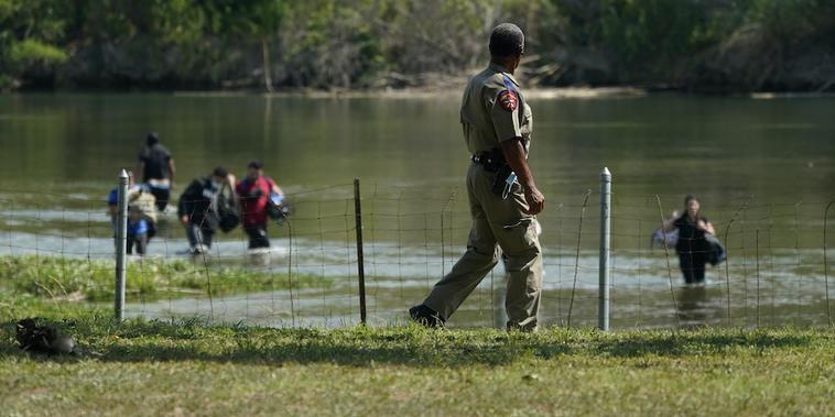 Un oficial de Seguridad Pública de Texas observa mientras un grupo de inmigrantes indocumentados cruza el Río Grande en Del Rio, Texas, el miércoles 16 de junio.