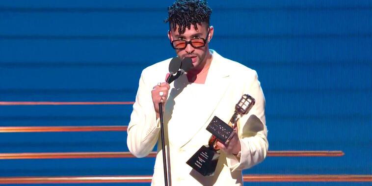 """Bad Bunny acepta su premio a """"Top Latin Album del Año"""" durante los Premios Billbaord 2021 en el Watsco Center de Miami, Florida el 23 de septiembre en el vistiendo una traje satinado de color blanco, camiseta blanca, gafas de sol de marco negro y zapatos"""
