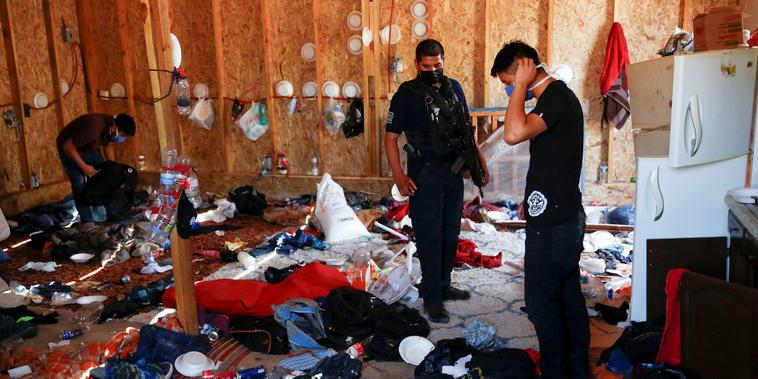 Agentes de policía en medio de las pertenencias de los migrantes rescatados de Centroamérica.