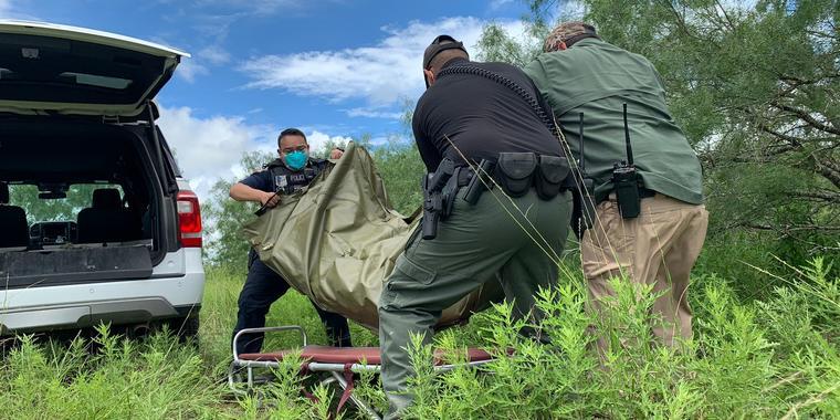 Agentes del condado de Brooks cargan el cuerpo de un migrante.